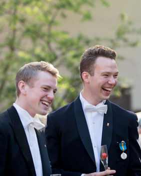 Two laughing students in formal wear.