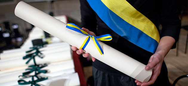 A diploma, rolled up with a blue and yellow ribbon around it.