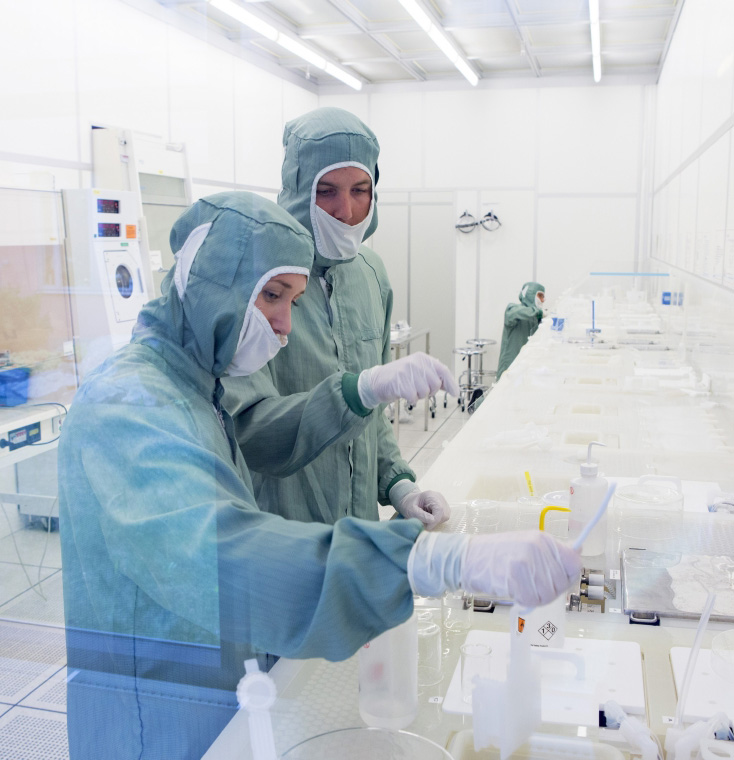 Two students in protective clothing working in a laboratory on campus