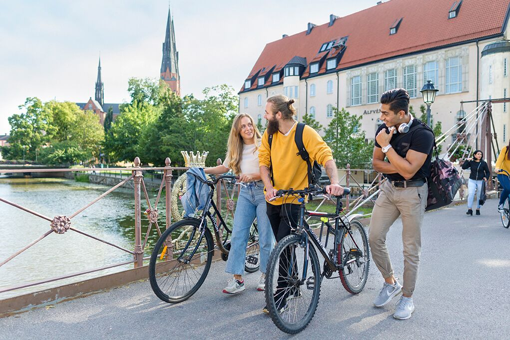 Students walking with bikes on a bridge, with the cathedral seen in the background